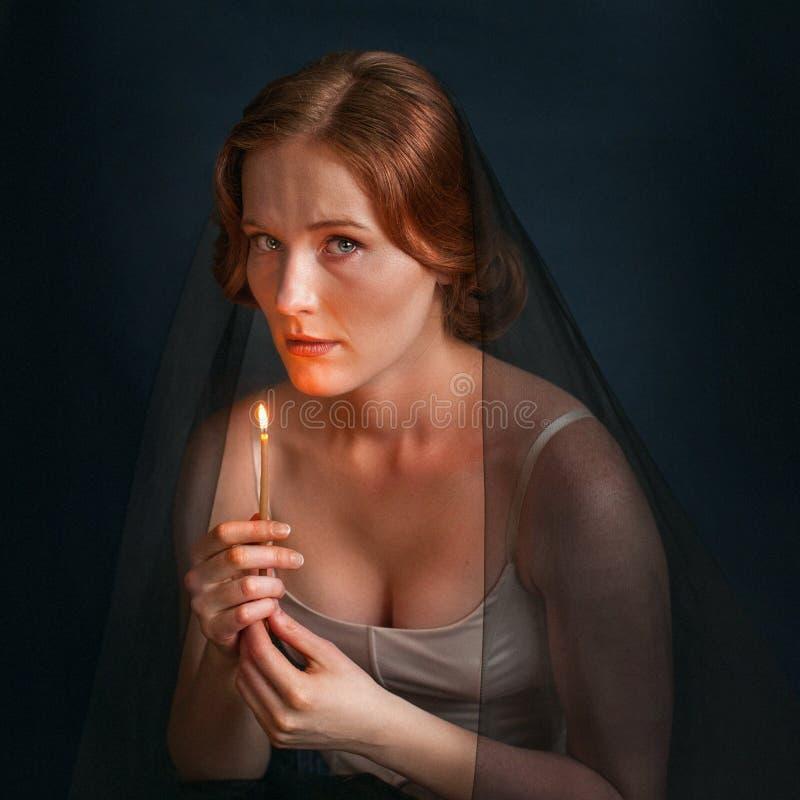 Kobieta z świeczką pod przesłoną Halloweenowa fotografia obraz stock