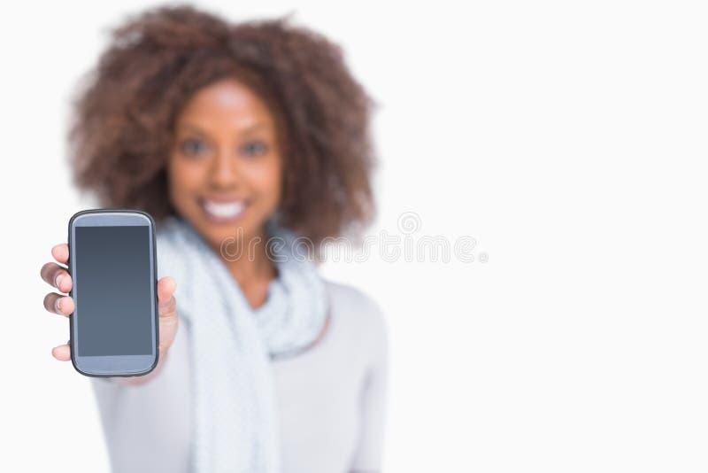 Kobieta z afro pokazuje jej smartphone obrazy royalty free