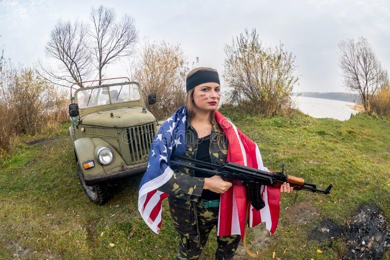 Kobieta z amerykańską flagą i strzelbą w pobliżu samochodu wojskowego obrazy royalty free