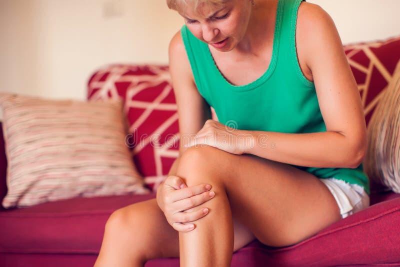 Kobieta z bólem kolana w domu Koncepcja ludzi, medycyny i opieki zdrowotnej fotografia stock