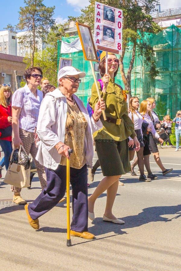 Kobieta z badik z portretem antenat uczestnik Wielka Patriotyczna wojna chodzi wzdłuż kolumny «Mnie obrazy stock