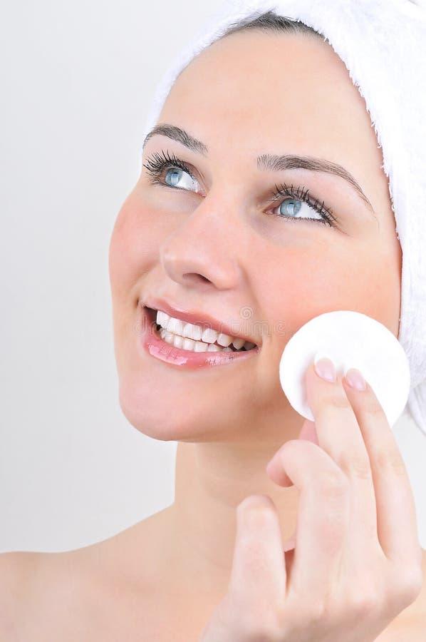 Kobieta z bawełnianego mopu cleaning jej twarz obrazy stock