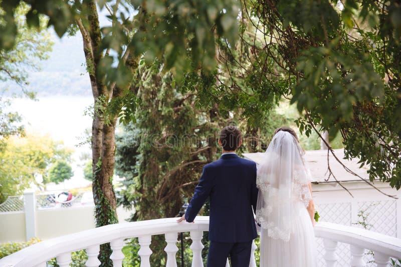Kobieta z białą koronkową przesłoną i ślubną suknią trzyma mężczyzna w garniturze, para stoi na fotografia royalty free