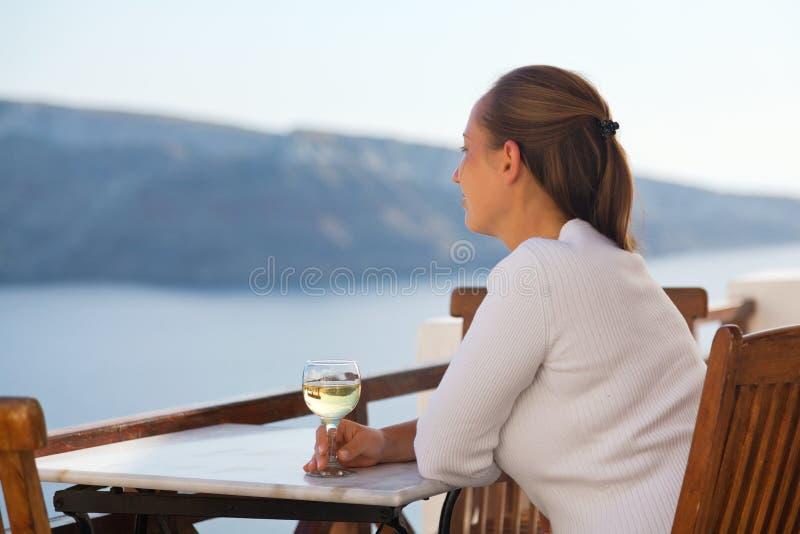 Kobieta z białym winem w Oia, Santorini obraz stock