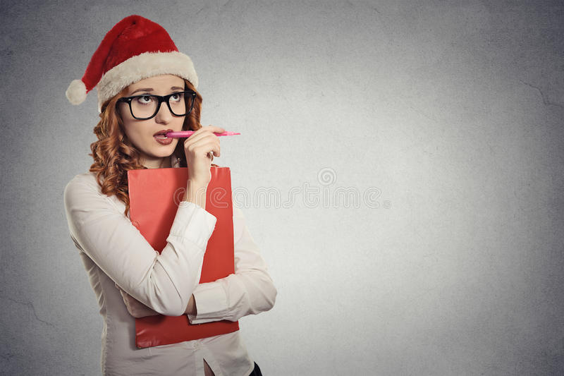 Kobieta z boże narodzenie kapeluszem pozuje w pracownianym główkowaniu prezentów pomysły obraz stock