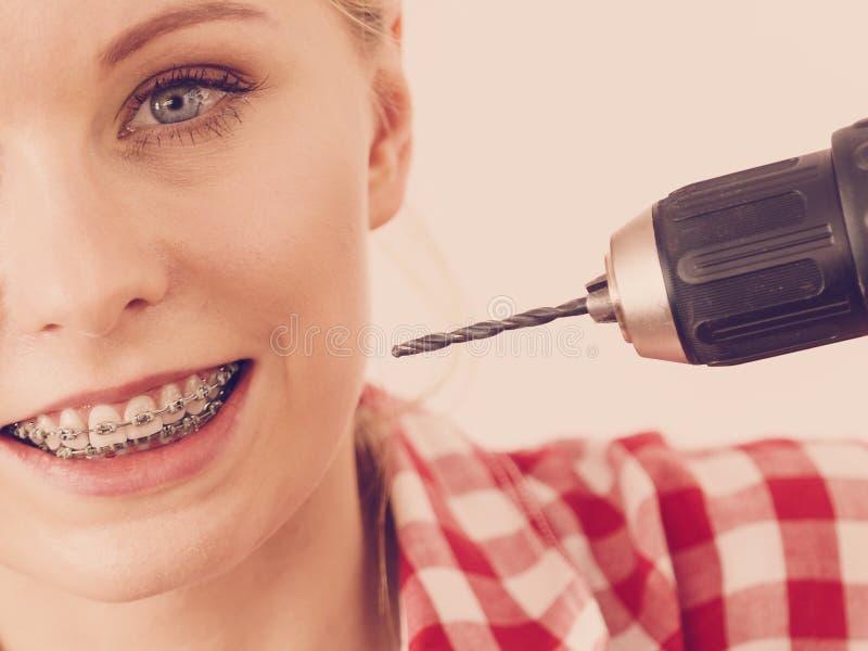 Kobieta z brasami używać świder na jej zębach fotografia stock