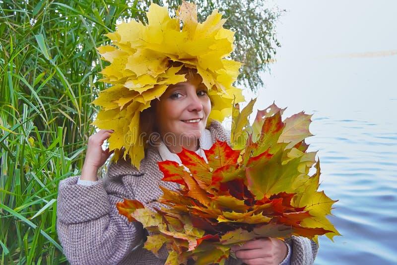 Kobieta z bukiet jesieni klonowymi liśćmi zdjęcia royalty free