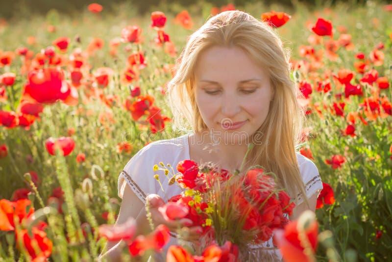 Kobieta z bukietem wśród maczka pola przy zmierzchem fotografia stock