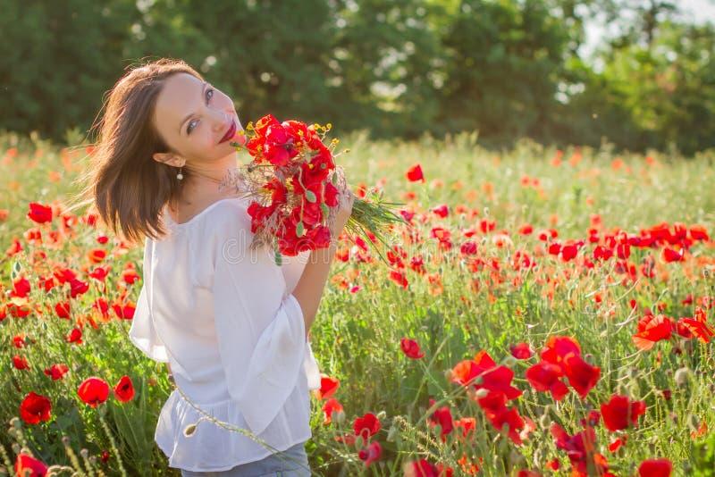 Kobieta z bukietem wśród maczka pola przy zmierzchem zdjęcie stock