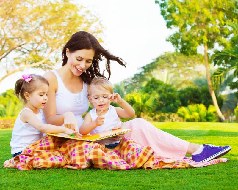 Kobieta z córką i synem czyta bajkę obraz royalty free