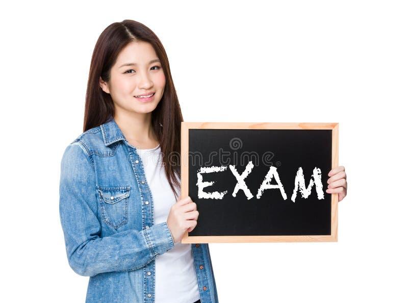 Kobieta z chalkboard pokazuje słowo egzamin obraz stock