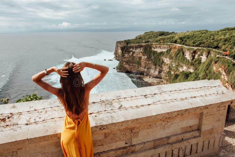 Kobieta z ciemnymi włosami w eleganckiej żółtej sukience podziwiająca panoramiczny widok oceanu fotografia stock