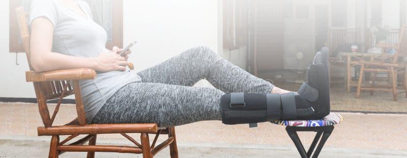 kobieta z czerni obsadą na nogi obsiadaniu na drewnianym krześle, ciało uraz zdjęcie royalty free