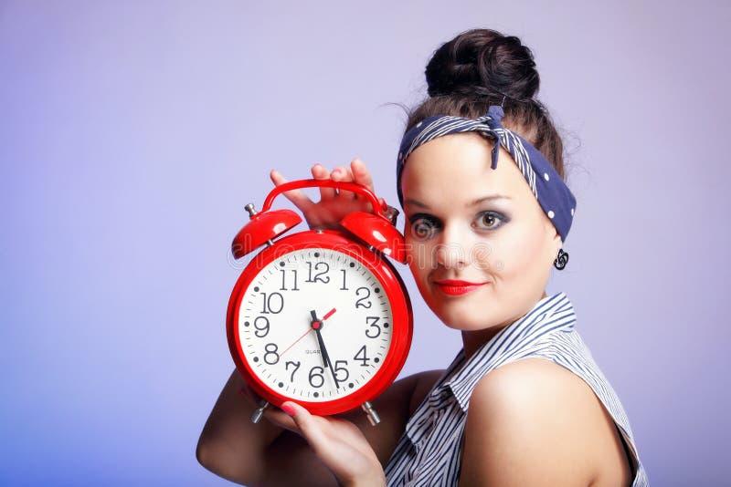 Kobieta z czerwień zegarem. Czasu zarządzania pojęcie. zdjęcia royalty free