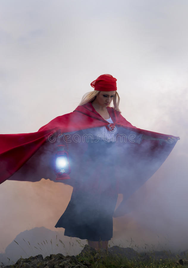 Kobieta z czerwoną peleryną i lampa w zmierzchu zaświecamy obraz stock