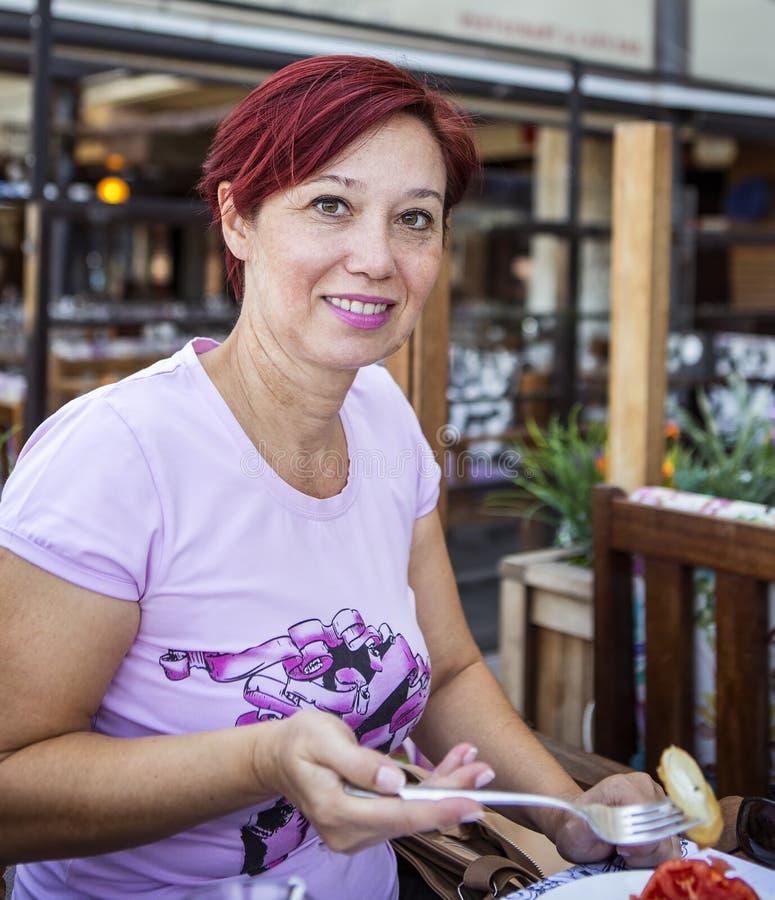 Kobieta z czerwony włosianym mieć śniadanie obrazy stock