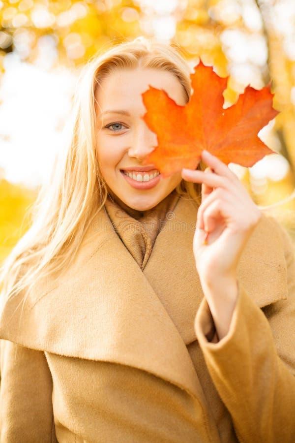 Kobieta z czerwonym marple liściem w jesień parku obraz royalty free