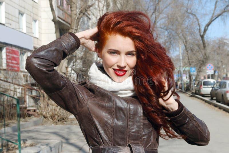 Kobieta z długie włosy w skórzanej kurtce uśmiecha się plenerowego obraz stock
