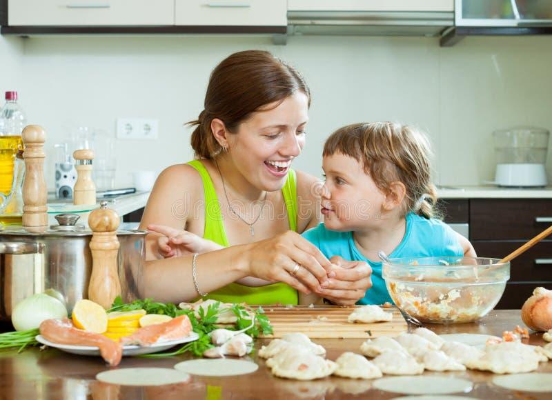Kobieta z dziewczyny uśmiechniętymi kluchami łowi kucharstwo wpólnie przy ho obrazy stock