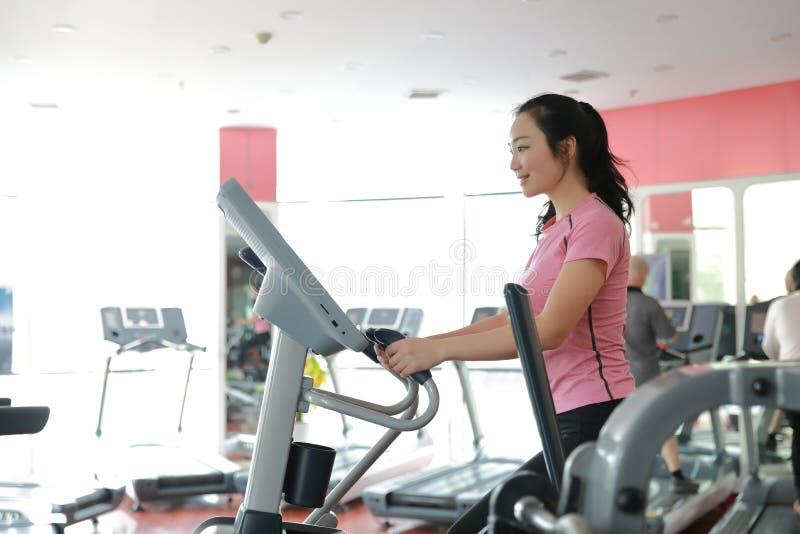 Kobieta z elliptical przecinającym trenerem przy gym Mięśniowy, wnętrze zdjęcia royalty free