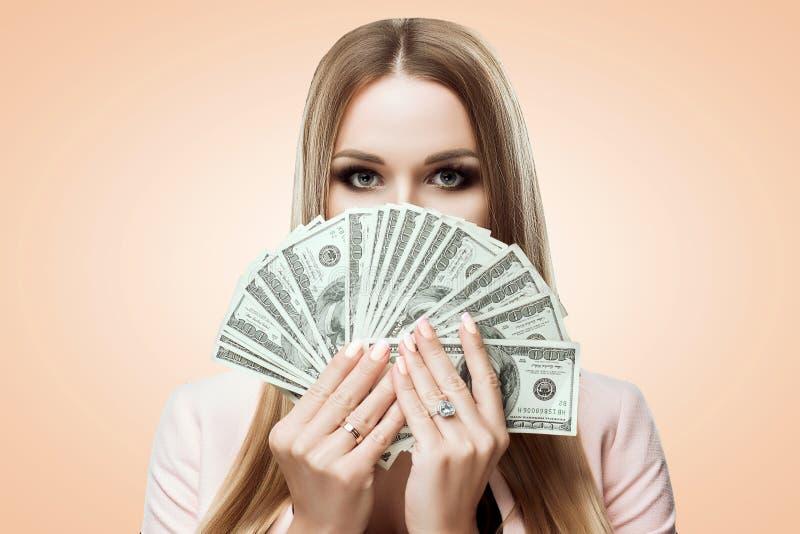 Kobieta z fan pieniądze w ona ręki Piękno portret młoda dziewczyna zakrywa jej twarz z pieniądze Rachunki 100 USD zdjęcie stock