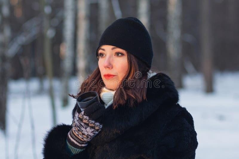 Kobieta z filiżanką herbata w zima parku zdjęcia stock