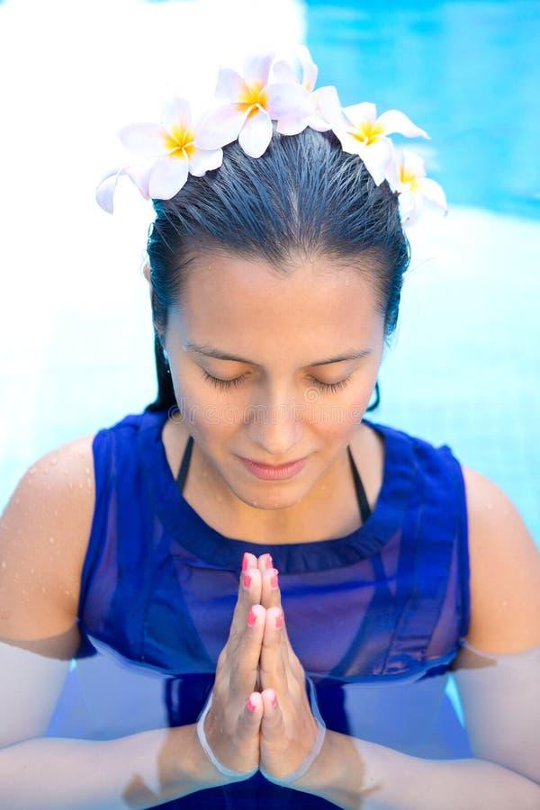 Kobieta z frangipani kwitnie w jej włosy, modli się pozę w pływackim basenie obraz royalty free
