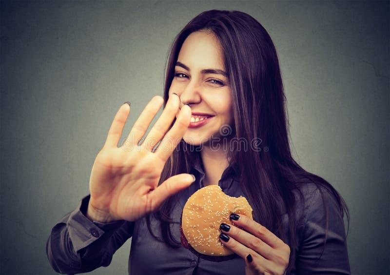 Kobieta z hamburgeru odrzucać radzi na zdrowym łasowaniu zdjęcie stock