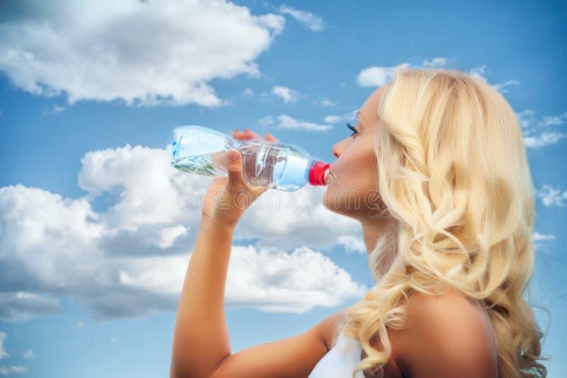 Kobieta z jabłkiem przeciw nieba tłu zdjęcia royalty free