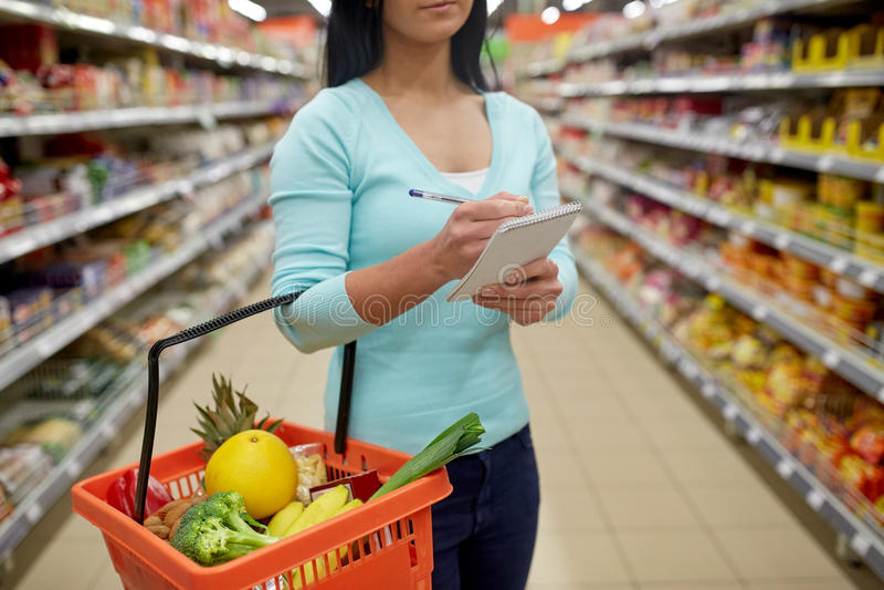 Kobieta z jedzeniem w zakupy koszu przy supermarketem obraz royalty free