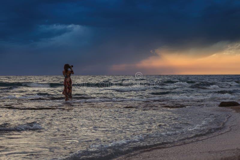 Kobieta z kamerą w dennym pobliskim wybrzeżu Grecka wyspa w pogodzie sztormowej Ja ` s pada na horyzoncie zdjęcia stock