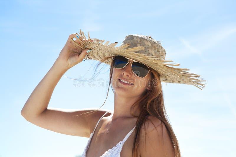 Kobieta z kapeluszem i okularami przeciwsłonecznymi zdjęcie royalty free