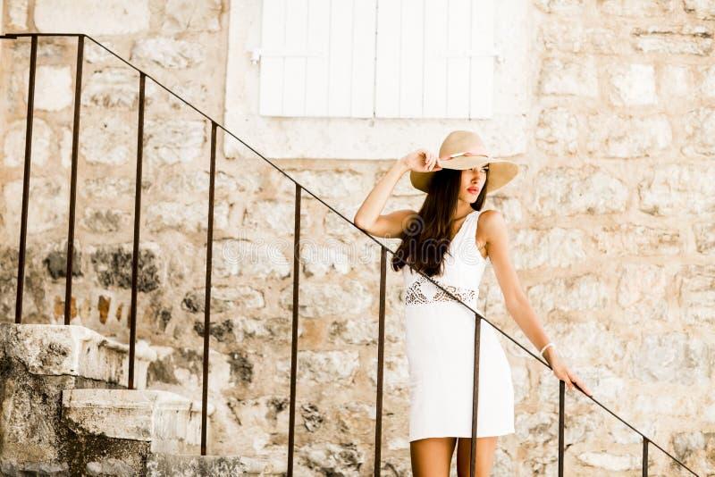 Kobieta z kapeluszową pozycją na schodkach plenerowych fotografia stock
