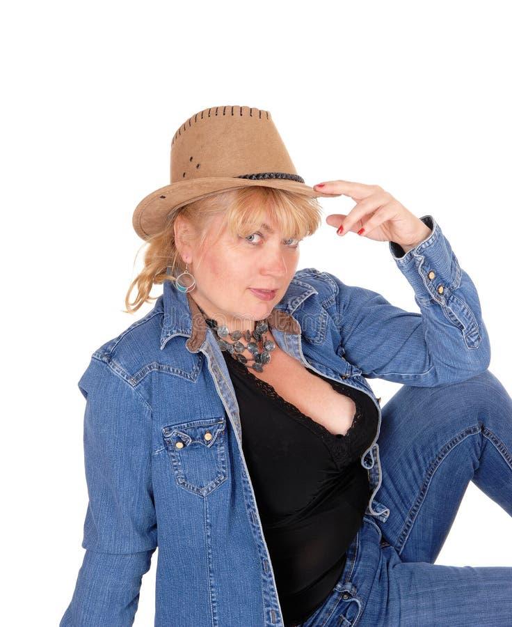 Kobieta z kapeluszowym obsiadaniem na podłoga zdjęcia stock