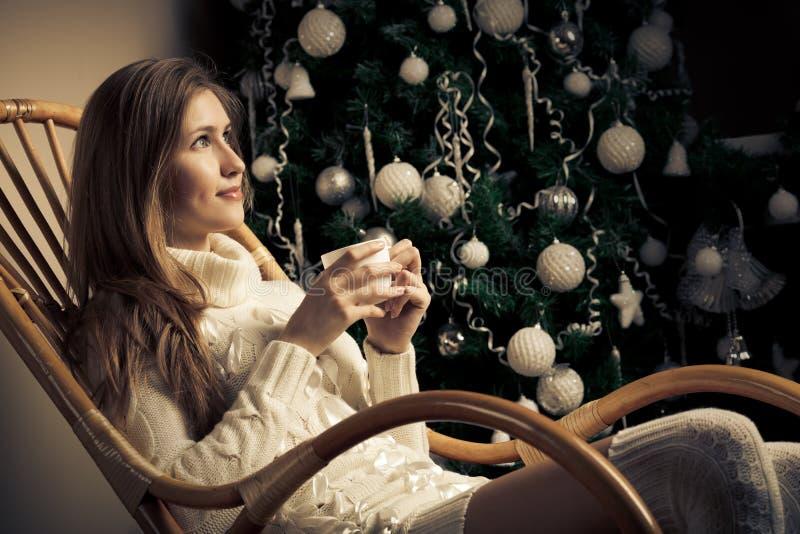 Kobieta z kawą w krześle. Bożenarodzeniowy decorati zdjęcie royalty free