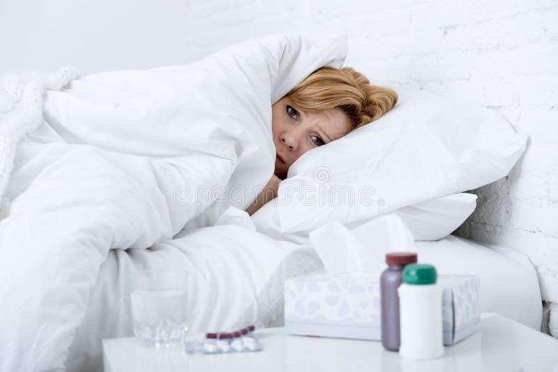 kobieta z kichnięcie nosem używać tkankę na łóżkowego cierpienia zimnym grypowym wirusie ma medycyny zdjęcia stock