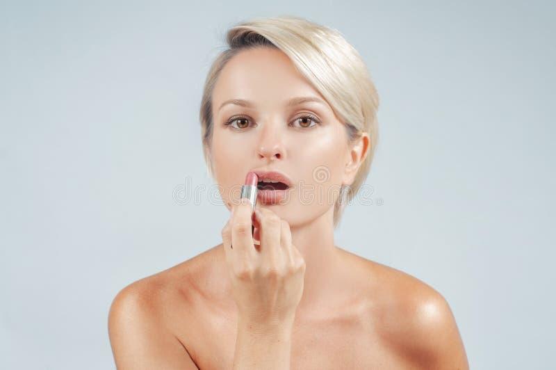 kobieta z kijem Piękna kobieta stosuje pomadkę patrzeje lustro obrazy stock