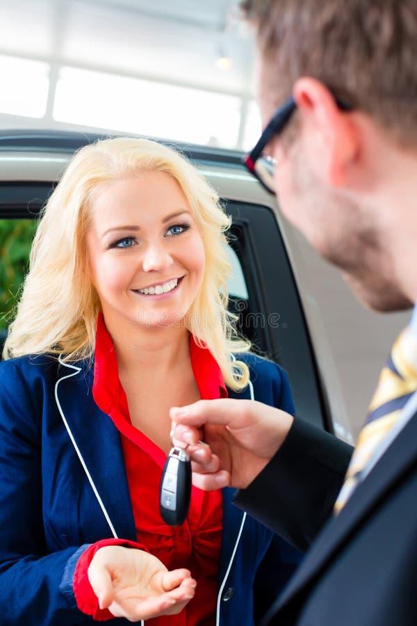 Kobieta z kluczem nowy samochód w przedstawicielstwie firmy samochodowej obraz stock