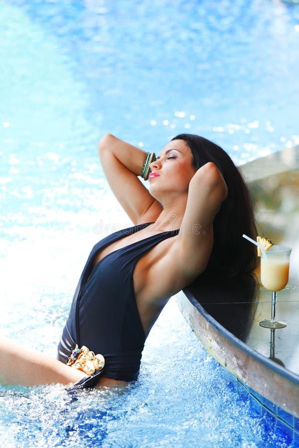 Kobieta z koktajlem w pływackim basenie zdjęcia royalty free