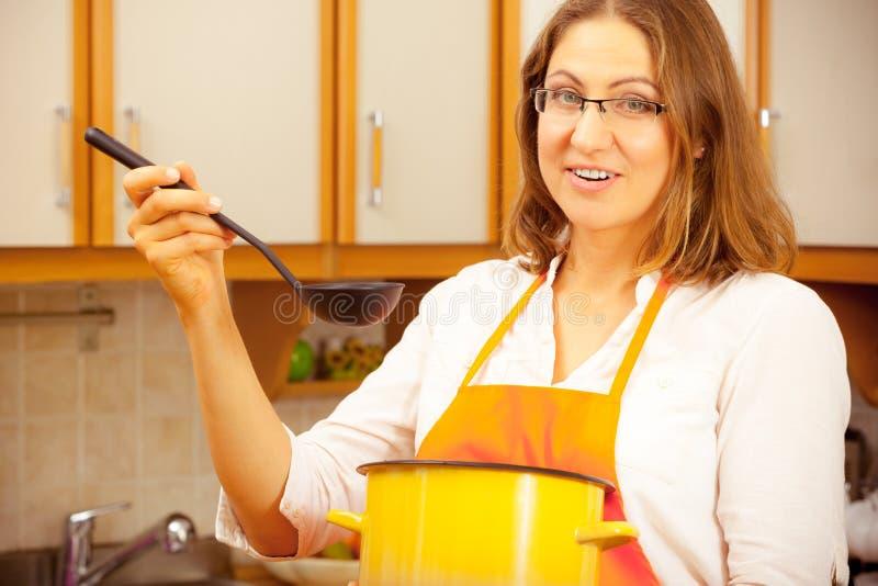 Kobieta z kopyścią i garnkiem w kuchni obrazy royalty free