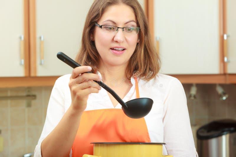 Kobieta z kopyścią i garnkiem w kuchni fotografia stock