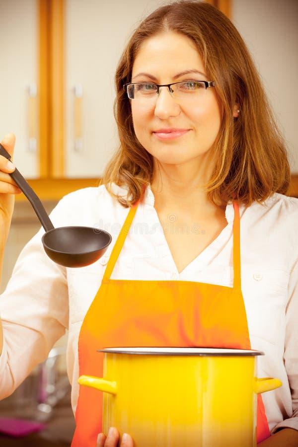 Kobieta z kopyścią i garnkiem w kuchni obraz stock