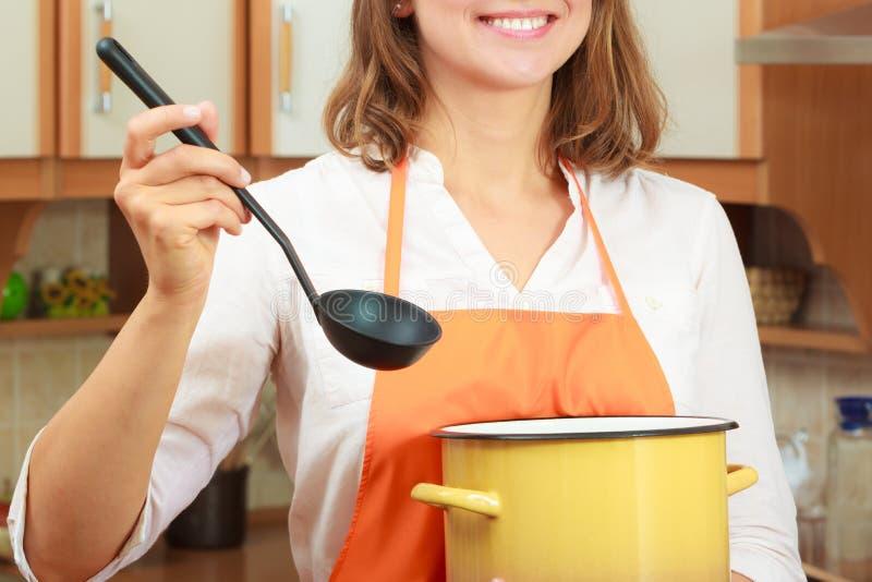 Kobieta z kopyścią i garnkiem w kuchni zdjęcie stock