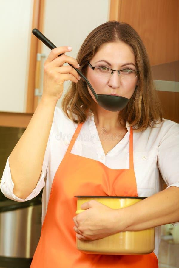 Kobieta z kopyścią i garnkiem w kuchni zdjęcia stock