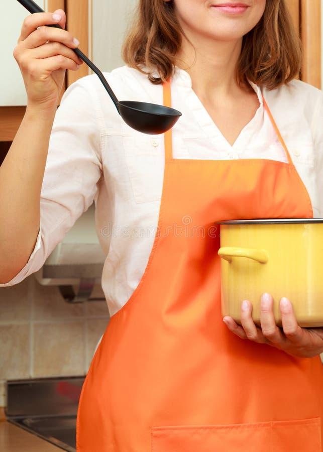 Kobieta z kopyścią i garnkiem w kuchni obraz royalty free