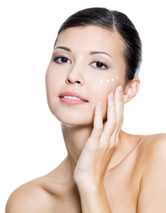 Kobieta z kosmetyczną śmietanką wokoło oka fotografia royalty free