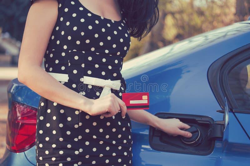 Kobieta z kredytową kartą otwiera paliwowego zbiornika samochód obraz royalty free