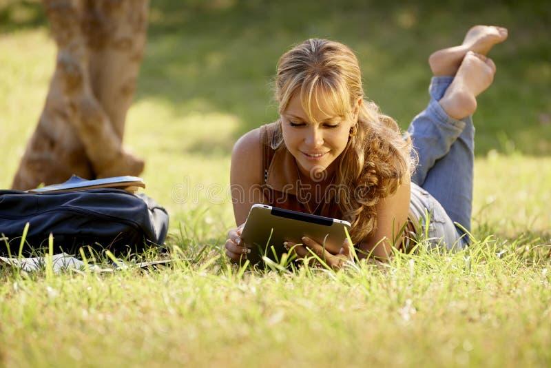 Kobieta z książkami i ipad studiowanie dla szkoła wyższa testa obrazy stock