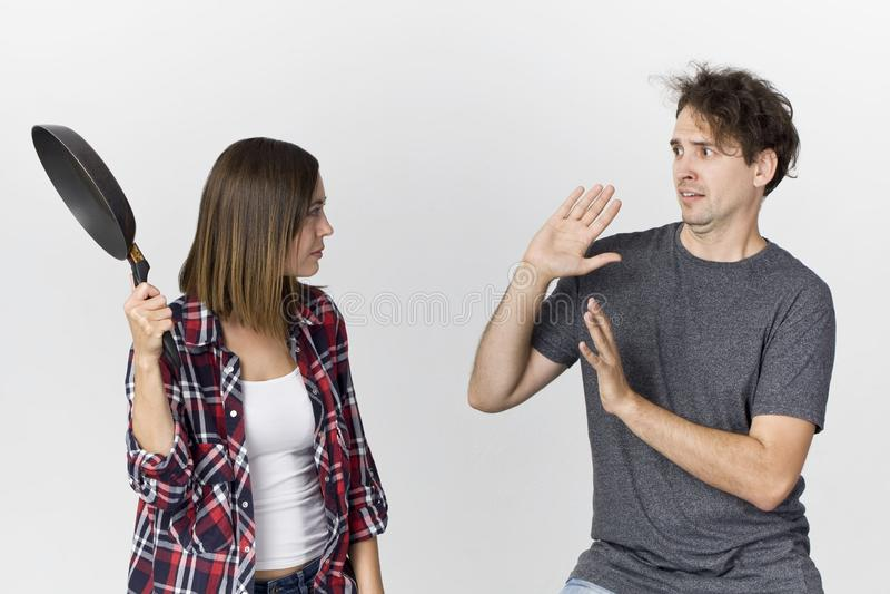 Kobieta z kulinarną niecką jest gniewny przy jej mężczyzna Para stoi a zdjęcia stock