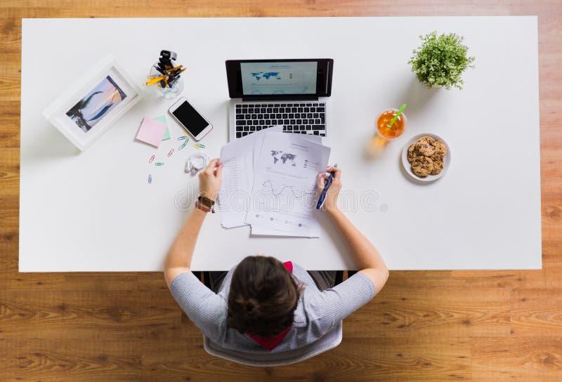 Kobieta z laptopem i papierami przy biuro stołem fotografia royalty free
